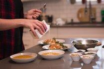 Mittelteil der Frau gießt Kochcreme in dal zu Hause — Stockfoto
