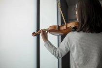 Vista posteriore della studentessa che suona il violino nella scuola di musica — Foto stock