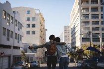 Vue arrière de jumeaux frères et sœurs debout dans la rue de la ville — Photo de stock
