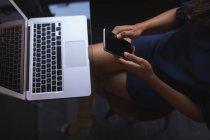 Femme d'affaires assis et utilisant le téléphone tout en travaillant sur ordinateur portable au bureau — Photo de stock