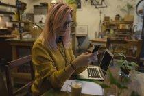 Giovane donna che utilizza un telefono cellulare alla caffetteria — Foto stock