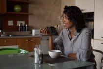 Happy woman having breakfast at home — Stock Photo
