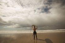 Surfer, die mit dem Surfbrett auf dem Kopf an einem sonnigen Tag — Stockfoto