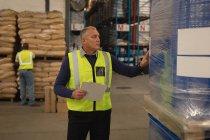 Mâle superviseur vérification de stock dans l'entrepôt — Photo de stock