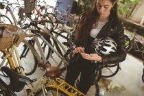 Красива жінка, за допомогою мобільного на стенді велосипеда — стокове фото