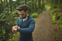 Handsome man checking time on smartwatch in forest — Stock Photo