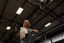 Інваліди зріла жінка, перевіряючи час при питної води в тренажерному залі — стокове фото