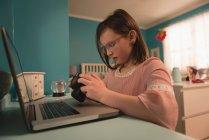 Fille regardant caméra tout en utilisant un ordinateur portable dans la chambre à coucher à la maison — Photo de stock