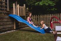 Irmãos brincando no jardim em um dia ensolarado — Fotografia de Stock