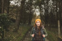 Front view of young female hiker standing in forest — Stock Photo
