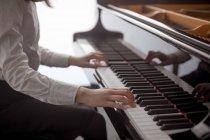 Розділ середині школярка грати на фортепіано в музичній школі — стокове фото