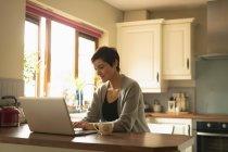 Donna usando il portatile in cucina a casa — Foto stock