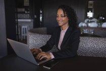 Mulher de negócios sorridente sentado e usando laptop na cafetaria do escritório — Fotografia de Stock