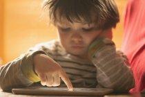 Primer plano del niño usando ficha digital en casa - foto de stock