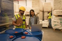 Staff interacting with each other over laptop in warehouse — Stock Photo