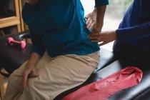 Розділ середині фізіотерапевт допомогу старших жінці з фізкультура — стокове фото