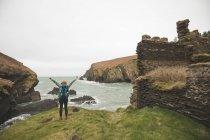 Vue arrière de la randonneuse bras répartis à côte de la mer — Photo de stock