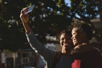 Twins siblings taking selfie with mobile phone in city street — Stock Photo