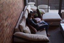 Couple utilisant une tablette numérique dans le salon à la maison — Photo de stock