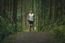 Homem correndo com seu cão na floresta exuberante — Fotografia de Stock