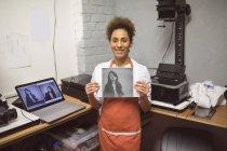 Portrait de photographe montrant des photos en studio photo — Photo de stock