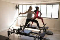 Two women exercising on stretching machine in fitness studio — Stock Photo