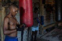 Männlicher Boxer binden Handpackung einerseits im Fitness-studio — Stockfoto