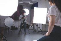 Fotógrafo do sexo feminino clicando fotos do modelo no estúdio de fotografia — Fotografia de Stock