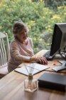 Donna anziana che utilizza un computer desktop a casa — Foto stock