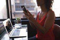 Mujer de negocios sentada y usando el teléfono mientras trabaja en la computadora portátil en la oficina - foto de stock