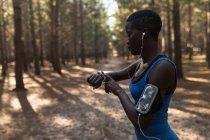 Atleta femenina comprobando su smartwatch en el bosque - foto de stock