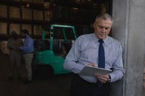 Male manager writing on a clipboard in warehouse — Stock Photo