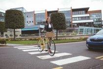 Женщина с велосипедом переходила дорогу — стоковое фото
