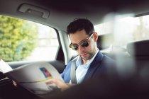 Intelligente Geschäftsmann lesen Zeitung in einem Auto — Stockfoto