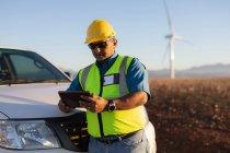 Инженер с помощью цифрового планшета на ветряной электростанции — стоковое фото