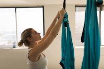 Donna che tiene swing fionda amaca in studio fitness — Foto stock
