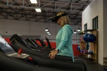 Disabled mature woman using virtual reality headset while exercising on treadmill — Stock Photo