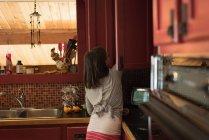 Jeune fille travaillant dans la cuisine à la maison — Photo de stock