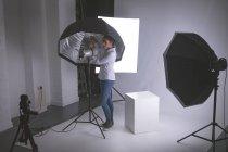 Female photographer adjusting strobe lights — Stock Photo