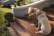Senior woman kissing dog on the entrance steps at home — Stock Photo