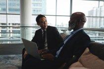 Deux hommes d'affaires avec ordinateur portable discuter avec le Bureau — Photo de stock