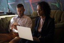 Ejecutivos de negocios que utilizan el portátil y el teléfono inteligente mientras están sentados sofá en la oficina - foto de stock