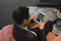Vue d'angle élevé d'homme d'affaires à l'aide de sa tablette numérique au bureau — Photo de stock