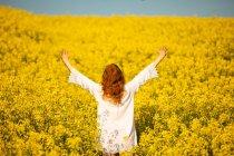 Vista posteriore della donna con la mano sollevata nel campo di senape in una giornata di sole — Foto stock