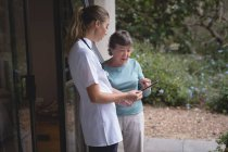 Physiotherapist and senior woman using a tablet at home — Stock Photo