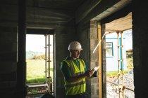 Ingeniero con tableta digital dentro del edificio en construcción se concentró - foto de stock
