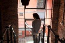 Вид сзади женщины с помощью ноутбука на лестнице дома — стоковое фото