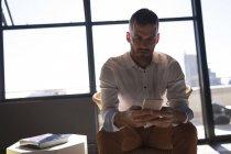 Empresário atento, usando o celular no escritório — Fotografia de Stock