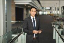 Ritratto di uomo d'affari con tablet digitale in ufficio — Foto stock