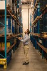 Чоловічий менеджер, використовуючи ноутбук під час перевірки запасів в склад — стокове фото